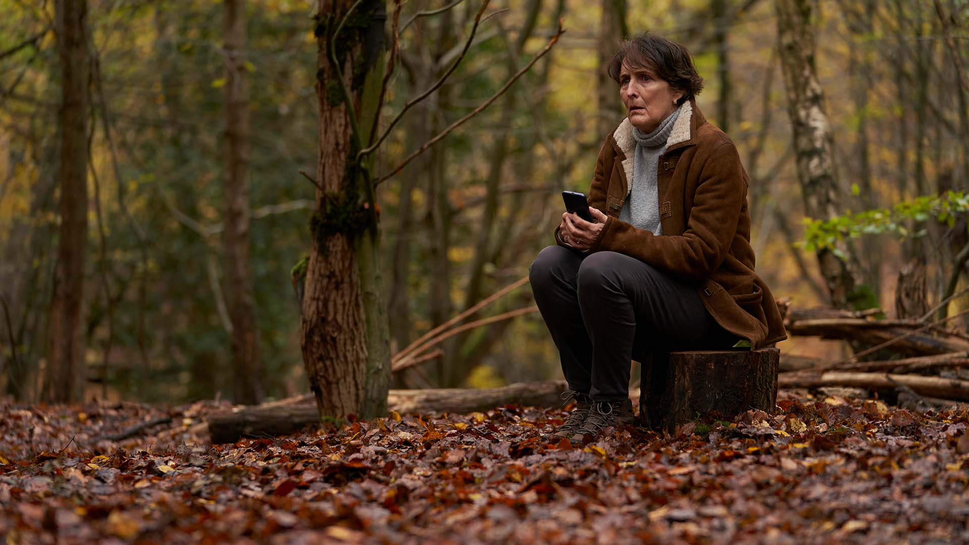 Fiona Shaw as Emma Chambers sitting in a wooded area looking concerned