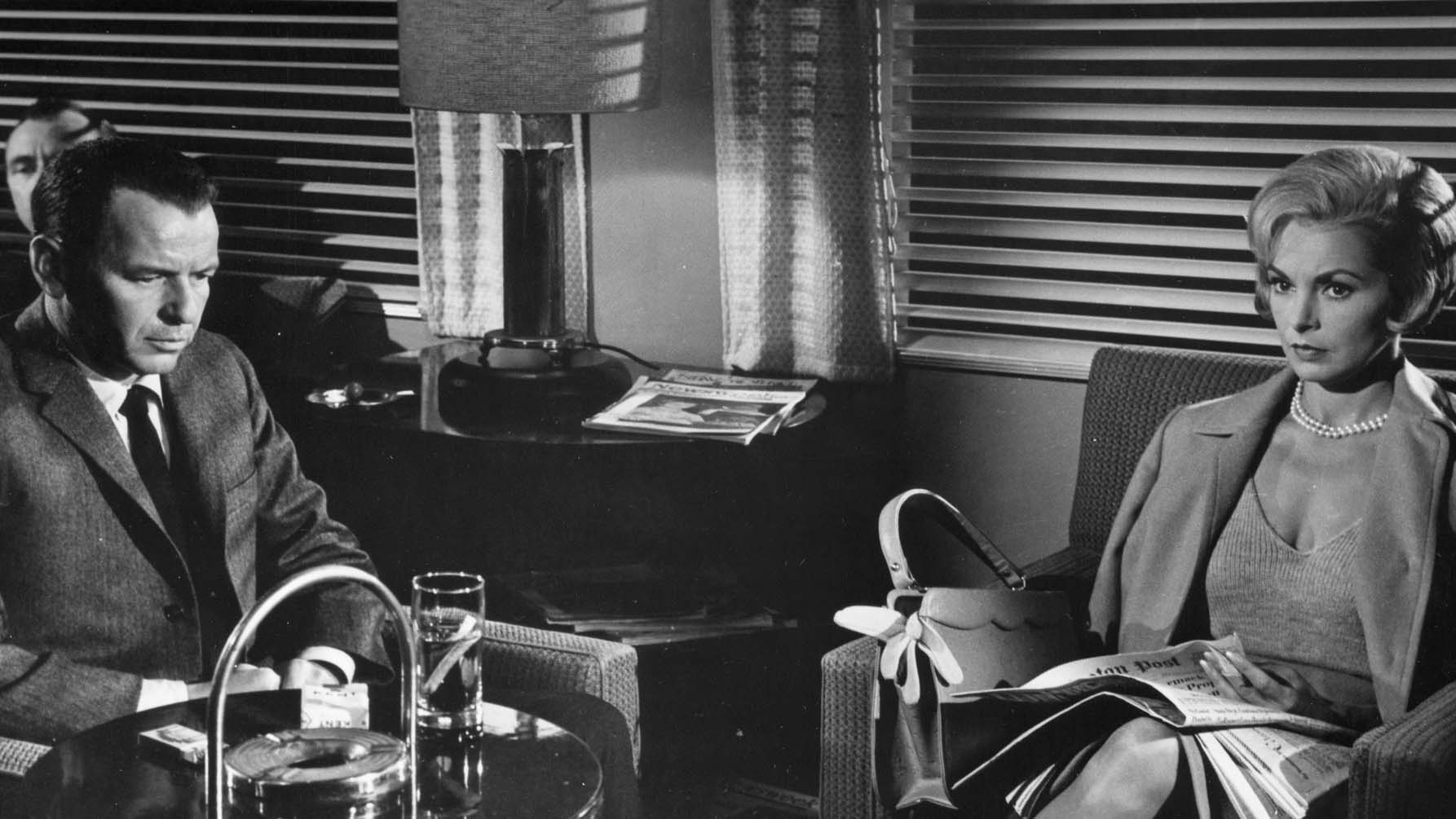 Black and white screen still from The Manchurian Candidate showing a man and a woman sitting in an office with serious expressions.