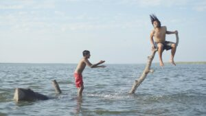 Two children playing on a branch protruding from the surface of a body of water